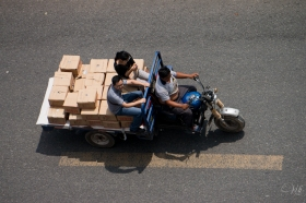 A typical Chinese tuktuk (3-wheeled cart). Notice the driver with his belly hanging out of his shirt (all men do this in the summer, rather than go topless), and the two passengers just perched on a bunch of boxes. No taxi? No problem; you can always find a ride in China